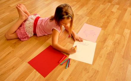 little girl coloring on a newly installed hardwood floor