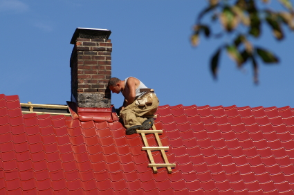Roofer installing a red metal roof.