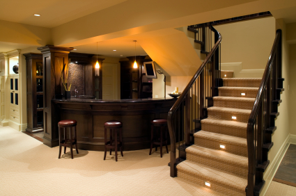 A newly remodeled basement with bar, television and lit staircase.