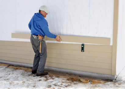 A contractor installing siding.