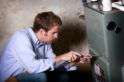 A contractor repairing a heating furnace.